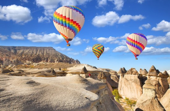 Hot air balloon flying over rock landscape at Cappadocia