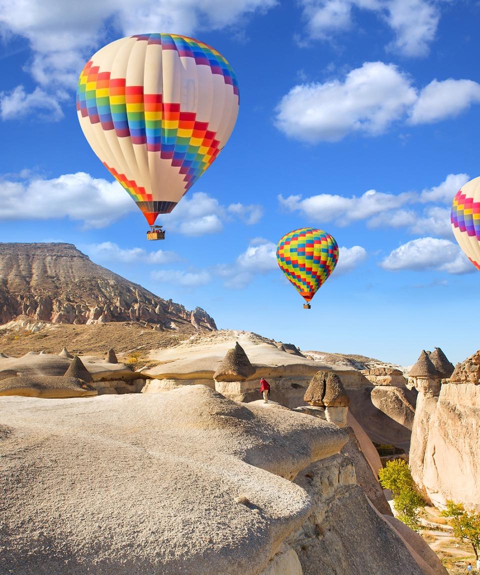 Hot air balloon flying over rock landscape at Cappadocia